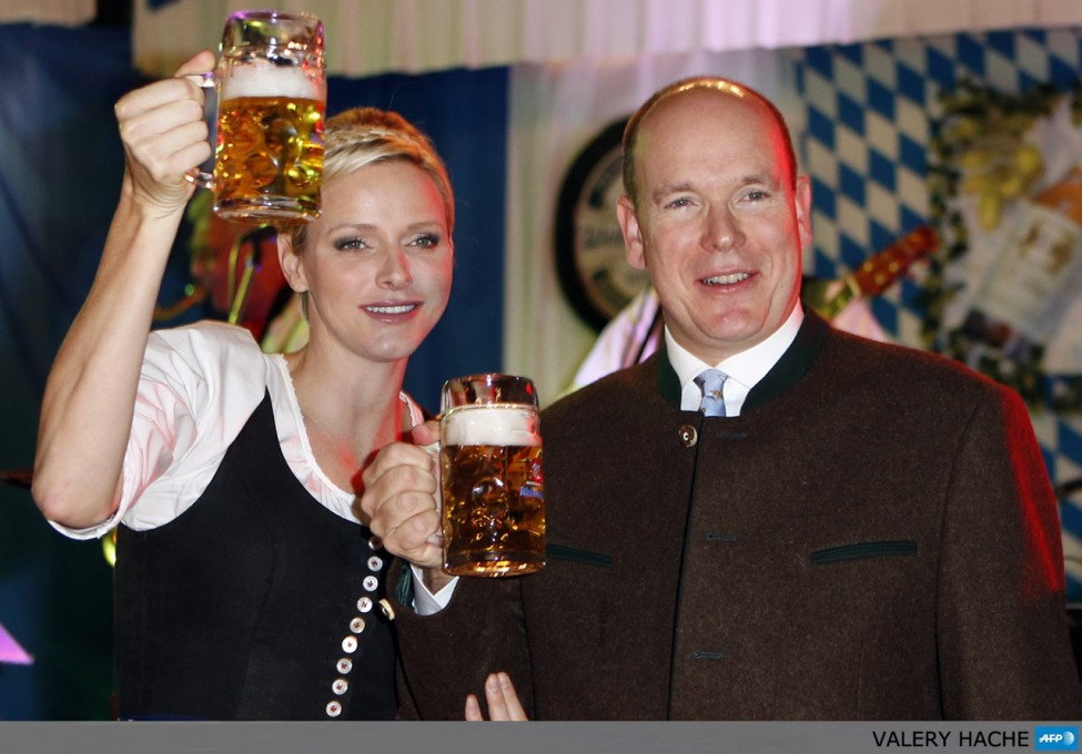 Prince's Albert II of Monaco (R) and Princess Charlene of Monaco (C) toast with beer mugs during the opening of the 7th edition of the 'Oktoberfest', on October 14, 2012, in Monaco. This annual event will run at the Cafe de Paris in Monaco until October 23.