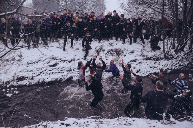 Shrovetide Football in Derbyshire, England. Rival teams the 'Up'ards and Down'ards' battle for the ball in the river during the annual Ash Wednesday 'no rules' football match on February 13, 2013, in Ashbourne, England. First played in the 17th Century between teams from opposite ends of the Derbyshire town, hundreds of participants aim to get a ball into one of two goals that are positioned three miles apart at either end of Ashboune. The match starts on Shrove Tuesday and can last until 10 PM. If a goal is scored before 6 PM, then a new ball is 'turned up' again and a new game started. If the goal is after 6 PM then the game ends for that day and continues into the next day - known as Ash Wednesday.