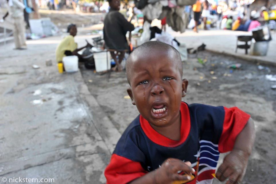 A child runs to me and pleads for food. His family is living on the streets after the earthquake destroyed their home.
