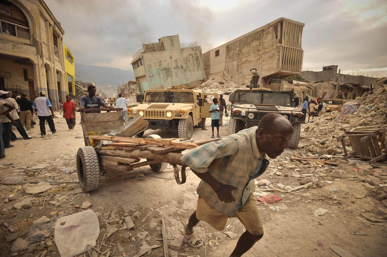 A man scavenges for materials to rebuild his home as US soldiers keep a security presence nearby. Port Au Prince Haiti.